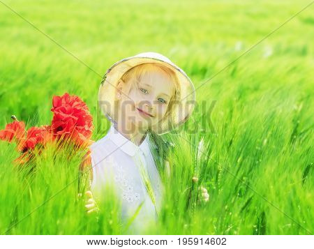 Happy little girl in a field of green rye. Portrait girl on nature background.