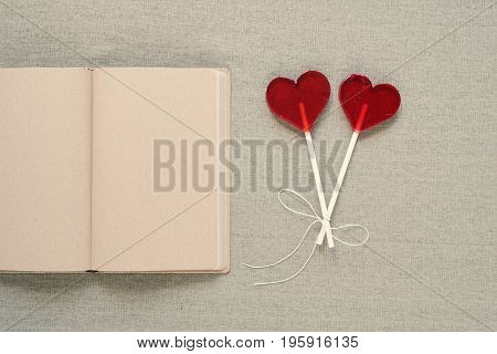 Two lollipops in the shape of a heart placed near an old diary with blank pages. Saint Valentine's Day, copy space.