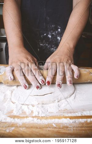 Close-up of woman rolling dough with rolling pin. Cooking concept.