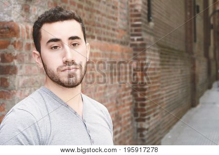 Portrait Of Young Man Against Brick Wall.