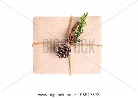 Brown Paper Craft Warped On Present Box Decorate With Pine Cone And Green Leaf Isolated On White Bac