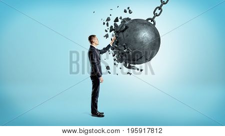 A businessman on blue background touching a wrecking ball when it crashes under his hand. Business consulting. Problem solver. Efficient crisis management.