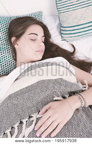 Close-up of beautiful young woman sleeping on her bed. Indoors.