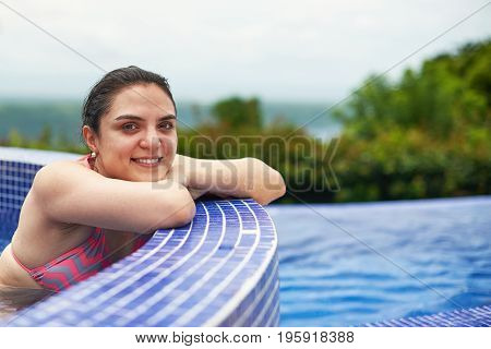 Smiling young woman portrait in outside pool