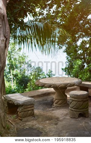 Small patio with stone table and chairs on tropical background