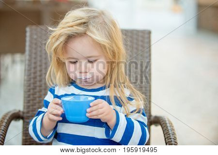 Adorable little boy with white milk mustache drinking cup of milk food and drink concept healthy food