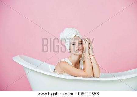 bath. girl with towel turban on head sitting in white bathtub on pink background spa and beauty relax and hygiene healthcare and housekeep copy space