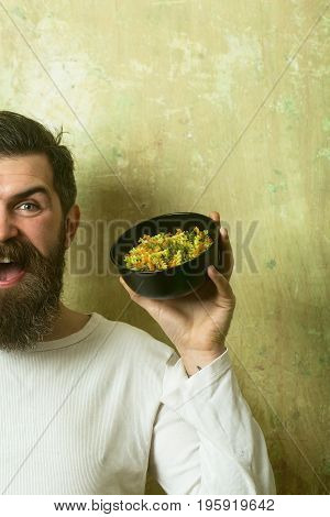 Cooking raw spaghetti in restaurant. Cook or chef bearded manwith bowl. Healthy food and dieting. Man smiling with pasta in hand. Hipster hold Italian macaroni.