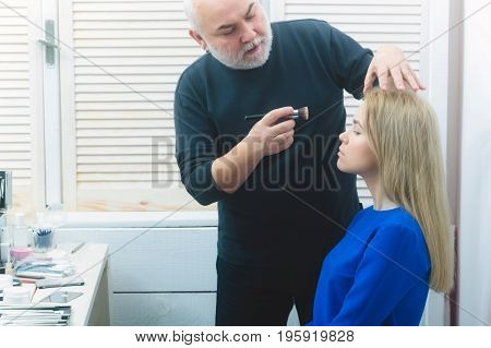 Beauty and fashion. Man applying foundation cream on girl face skin. Woman or pretty fashionable model with long blond hair in blue dress sitting at table with cosmetic kit in beauty salon.