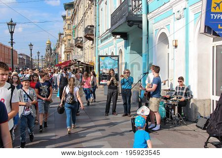 St. Petersburg, Russia - July 13 2017: Historic, picturesque street to Church on spilled blood full of pedestrians. Music band-group. Summer day, crowd of tourists. Lampposts, cafes, souvenir shops.