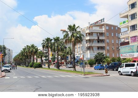 Antalya, Turkey - May 26 2017: A broad avenue with palm trees at the edge of the road, simple concrete residential building with shops and cafes on the ground floor. Street with cars. Crosswalk.