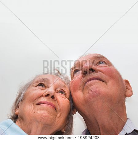Loving older couple looking up with a smile on white