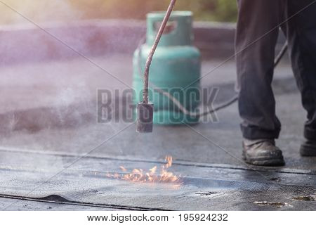 Asia worker installing tar foil on the rooftop of building. Waterproof system by gas and fire torching poster