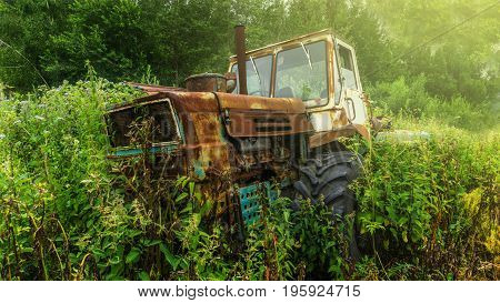 An old rusty derelict tractor parked in a farm yard in amongst overgrown grass and weeds