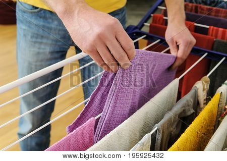 A man takes off towels from drying rack clothes.