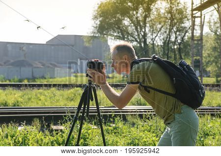 A man is filming outdoor. A camera is on a tripod. The man with a backpack is looking at the display.