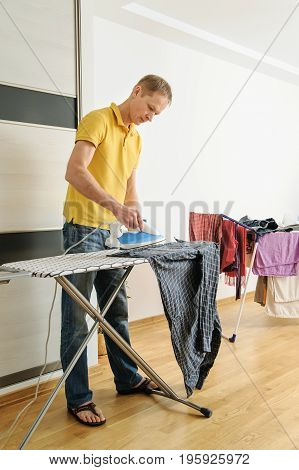 The man is ironing a shirt on the ironing board.