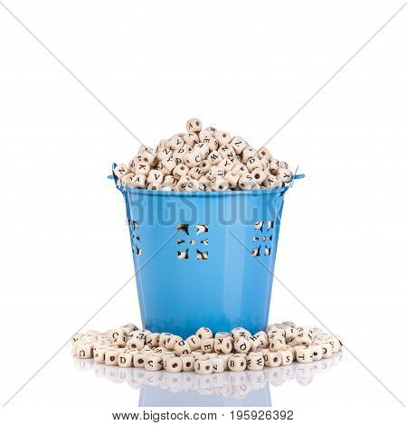 Pile Of Wooden Alphabet In Small Blue Metal Bucket. Studio Shot Isolated On White