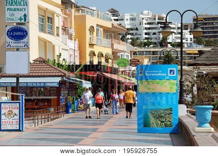 TORREMOLINOS, SPAIN - SEPTEMBER 3, 2008 - Tourists walking past bars and shops along the promenade Torremolinos Malaga Province Andalusia Spain Western Europe, September 3, 2008.