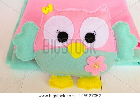 Felt owl on a white wooden background, rolls of pink and blue felt