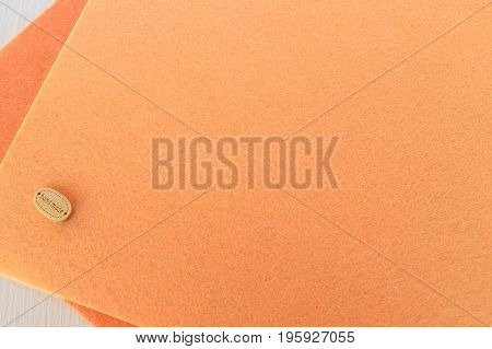Colorful sheets of felt and a button with the inscription handmade on white wooden background