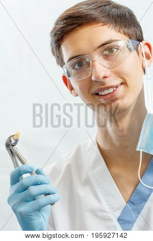 Portrait Of Handsome Male Dentist With Dental Tools In The Dental Clinic
