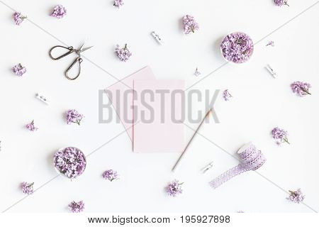 Stylish feminine workspace with lilac flowers paper blank accessories. Flat lay top view