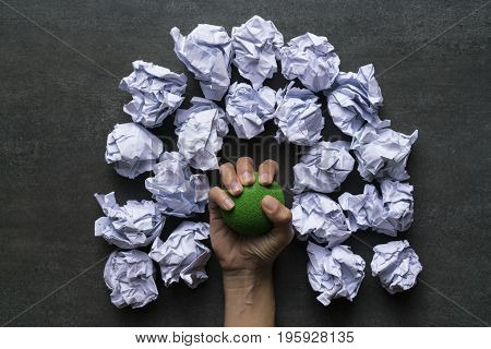 woman hand holding stress ball with crumpled paper background