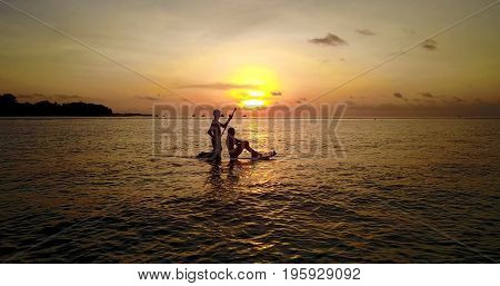 Aerial flying drone view of Maldives white sandy beach 2 people young couple man woman paddleboard rowing sunset sunrise on sunny tropical paradise island with aqua blue sky sea water ocean 4k.