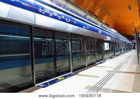 A metro train speeding past a metro station in Dubai United Arab Emirates