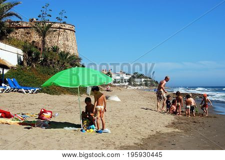 MARBELLA, SPAIN - SEPTEMBER 12, 2008 - Tourists relaxing on Playa de las Canas beach with the old watchtower to the rear Marbessa Marbella Malaga Province Andalusia Spain Western Europe, September 12, 2008.