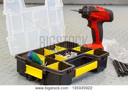 Red Cordless Screwdriver With Screws In A Storage Box
