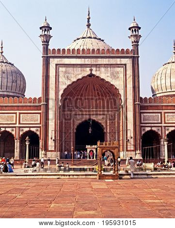 DELHI, INDIA - NOVEMBER 20, 1993 - Locals sitting around a pool at the Jama Masjid also known as the Friday mosque Delhi Delhi Union Territory India, November 20, 1993.
