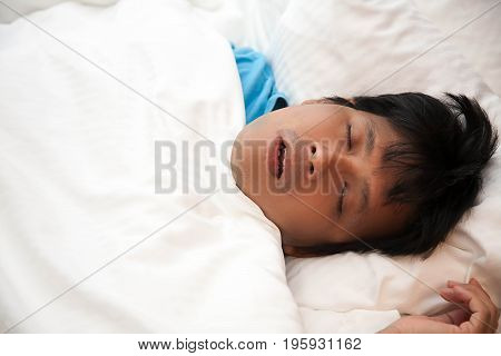 Asian man is snoring in bed and has sleep apnea Health care concept.
