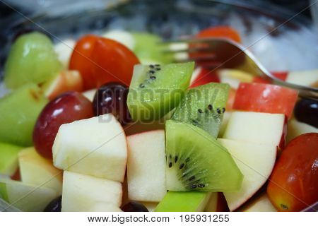 Diet, healthy fruit salad  with grape kiwi tomato red and green apple.