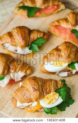 Vertical photo of mini croissants with egg chicken ham cheese tomato parsley and salmon on wooden board