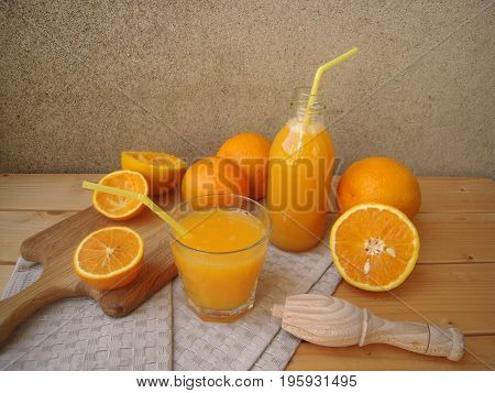 Orange juice freshly squeezed in glass and bottle, rustic set.