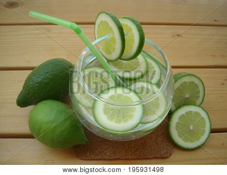 Lime water with sliced lime in a round bowl on a wooden surface