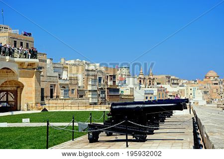 VALLETTA, MALTA - MARCH 30, 2017 - Row of cannons in Upper Barrakka Gardens with city buildings to the rear and tourists enjoying the view Valletta Malta Europe, March 30, 2017.