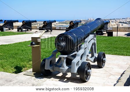 Cannons in Upper Barrakka Gardens with views across the harbour towards Vittoriosa Valletta Malta Europe.