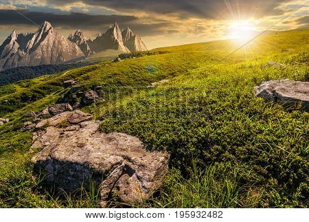 Meadow With Huge Stones On Top Of Mountain Range At Sunset