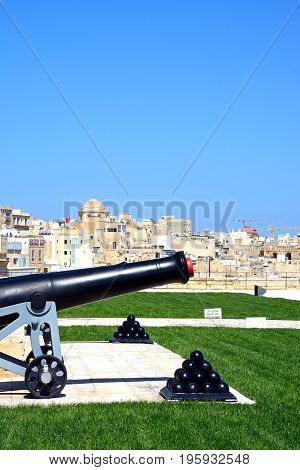 VALLETTA, MALTA - MARCH 30, 2017 - Cannon in Upper Barrakka Gardens with Cannonballs in the foreground and city buildings to the rear Valletta Malta Europe, March 30, 2017.