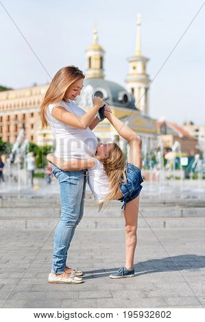 Mother and daughter doing exercise outdoors. Pregnant woman helps her little girl to stretch. Healthy lifestyle. Yoga. Girl gymnast stretching on the street. The girl is engaged in gymnastics