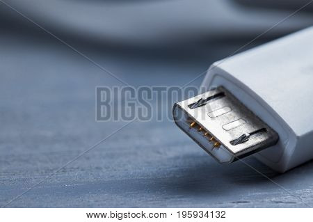 Closeup of micro usb smart phone power cable on a wooden background.