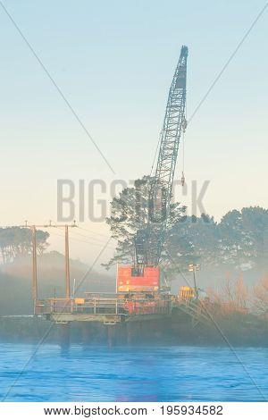 Early morning mist around a bridge building crane on the Manawatu river.