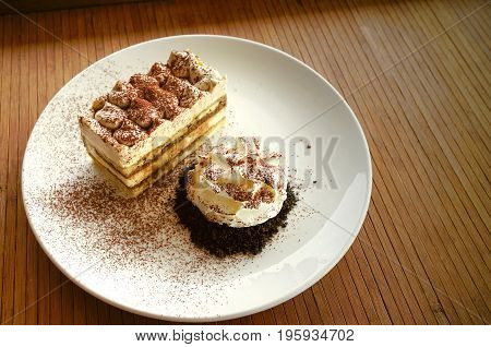 Tiramisu traditional Italian dessert with whipping cream in white plate on wooden table