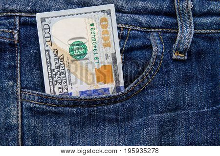 One Hundred American Dollars Bill In The Pocket Of Blue Jeans