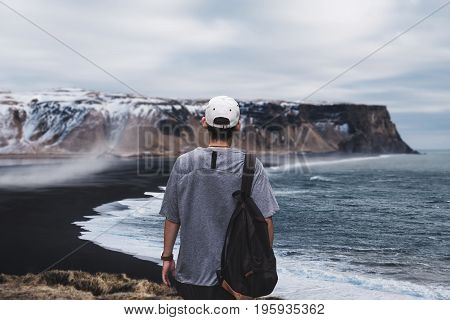 Young man with backpack standing on the cliff at Dyrholaey, Black Sand Beach in Iceland