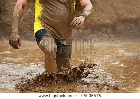 Mud race runners obstacle race runner in action