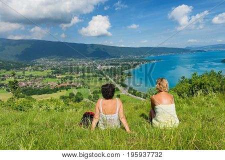 Two women watching the view of Lake Annecy
